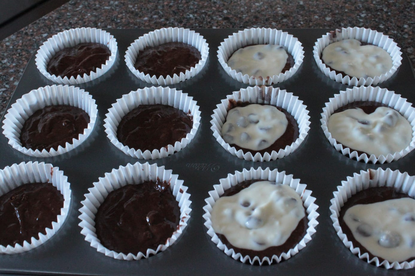 A cupcake tray half filled with black bottom cupcakes.
