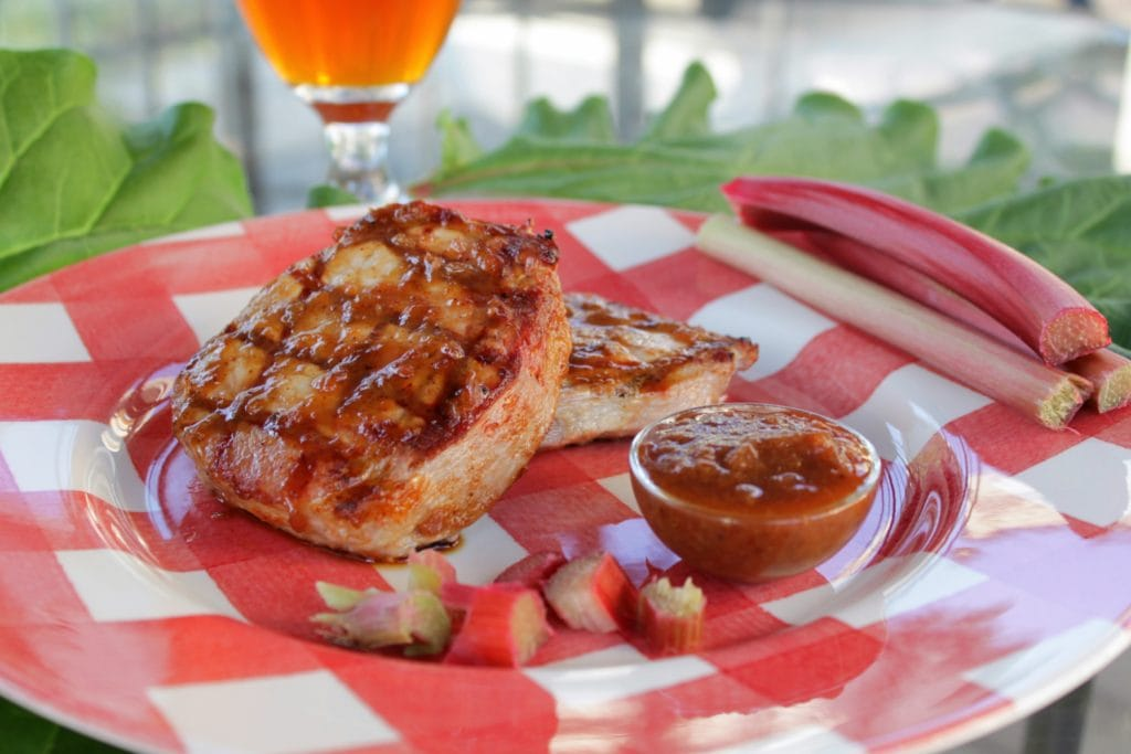 A perfectly grilled pork chop covered with brown rhubarb barbecue sauce.