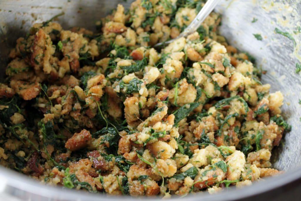 Spinach Balls - A bowl full of stuffing mixture dotted with spinach.