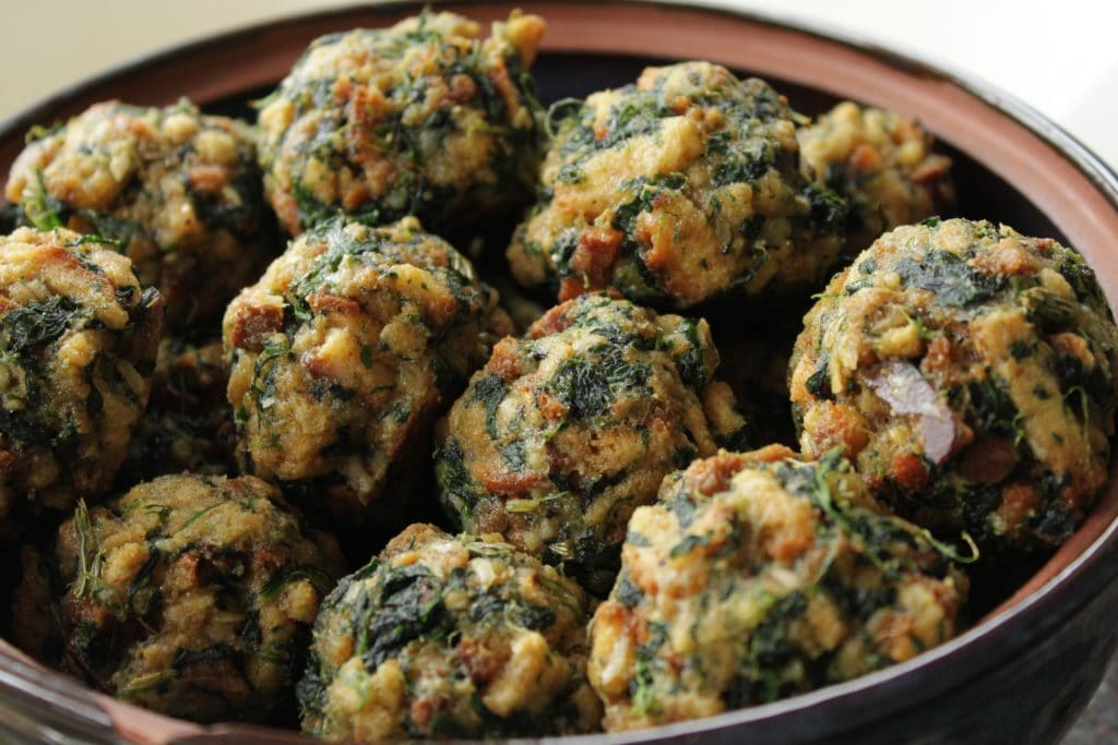 Spinach Balls - A bowl full of baked stuffing balls dotted with spinach.