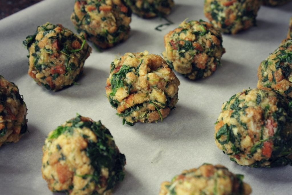 Spinach Balls - Stuffing balls dotted with spinach on a baking sheet.