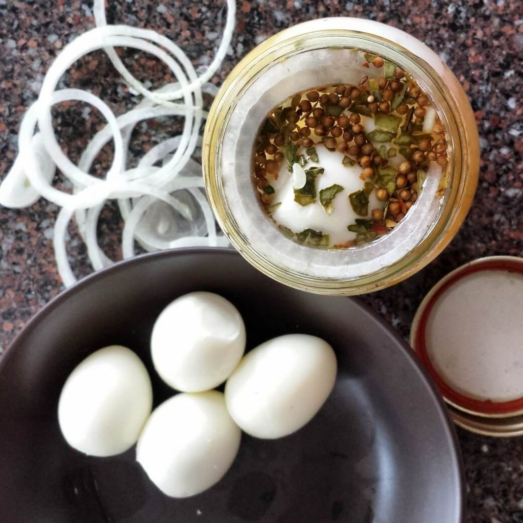A jar of pickling spices, some onions, and some hard boiled eggs.