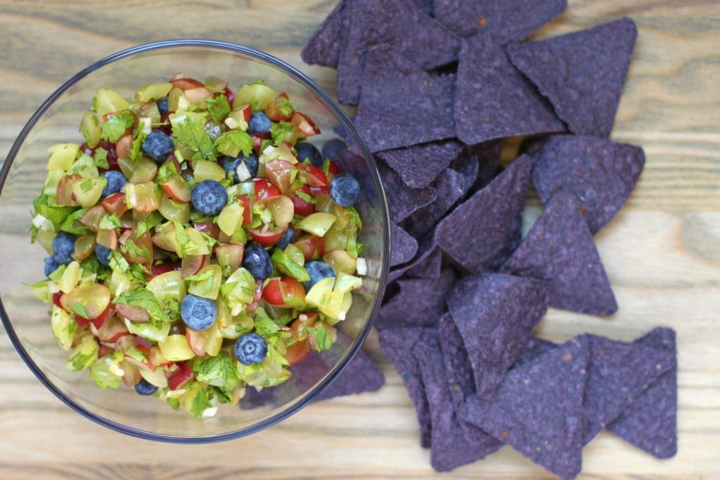 A bowl of salsa made from chopped green and red grapes with blueberries and purple corn chips.