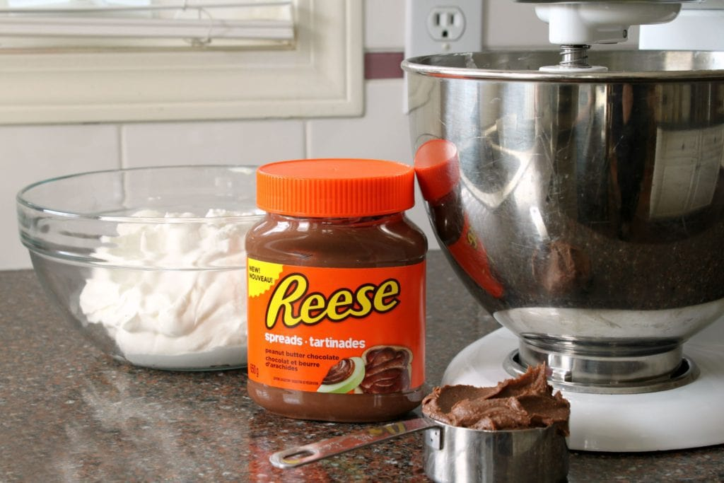 A jar of Reese's Chocolate Peanut Butter spread sits in front of a bowl of whipped cream.