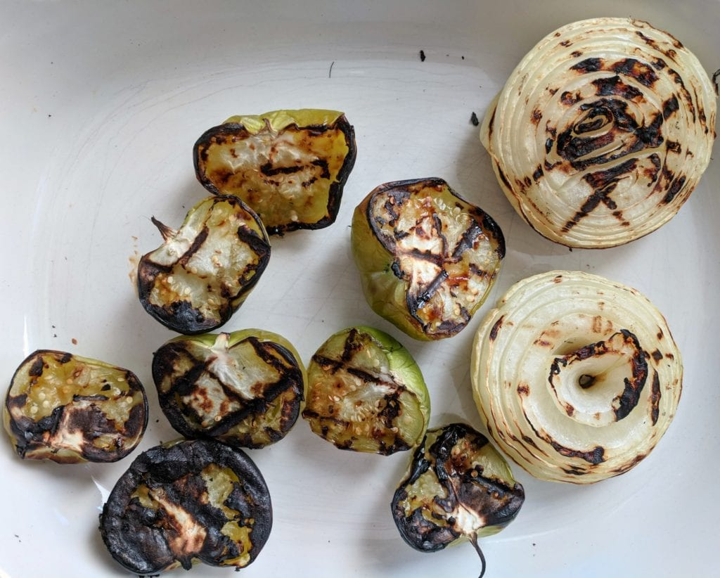 A platter of grilled tomatillos and onions