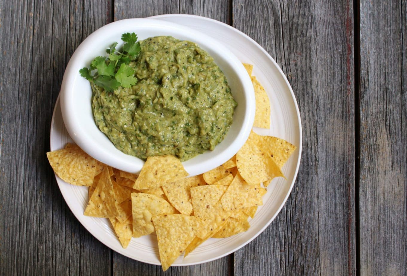 A Bowl of chunky green dip and some chips on the side