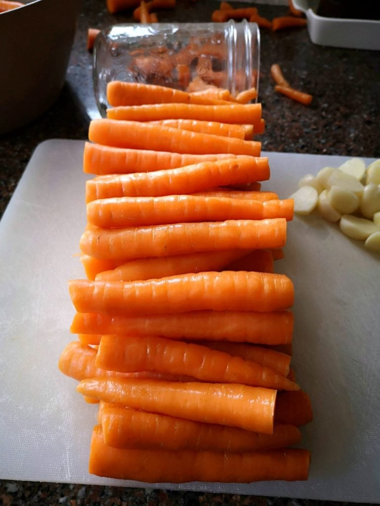 Pickled Carrots with Dill and Garlic - Bright carrots lined up and cut to size for pickling.