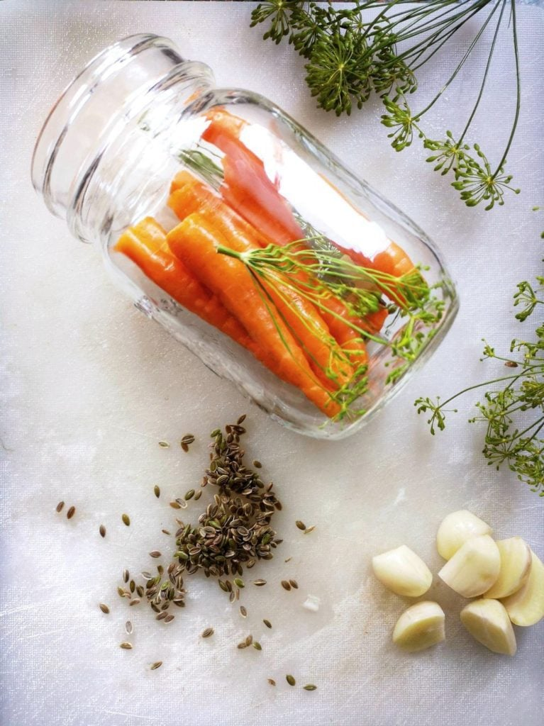Pickled Carrots with Dill and Garlic - A half packed jar of bright carrots, fresh dill, and garlic surrounded by more fresh dill and garlic.
