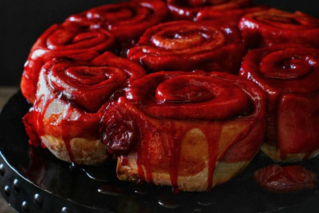 Sticky, sweet, sour...these Sourdough Plum Cinnamon Rolls are everything you wished them to be and more. Pillow-y soft sourdough rolls are stuffed with stewed red plums which combine with the brown sugar and cinnamon to make a striking sauce. #cinnamonrolls #cinnamonbuns #breakfast