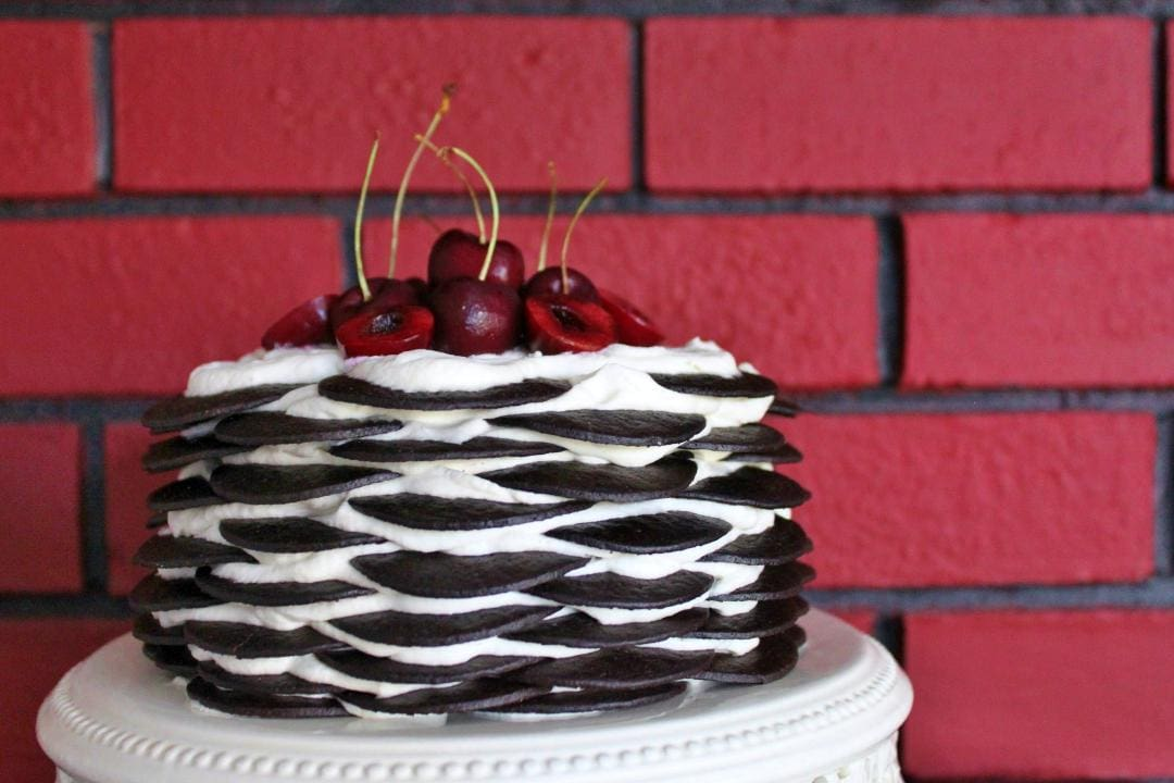 Deceptively stunning, super easy no bake Chocolate Biscuit Cake layered with amaretto spiked whipped cream. Top it with cherries or seasonal fruit to up the 'wow' factor. #3ingredients #cookingwithbooze #cake #nobakecake #birthdaycake