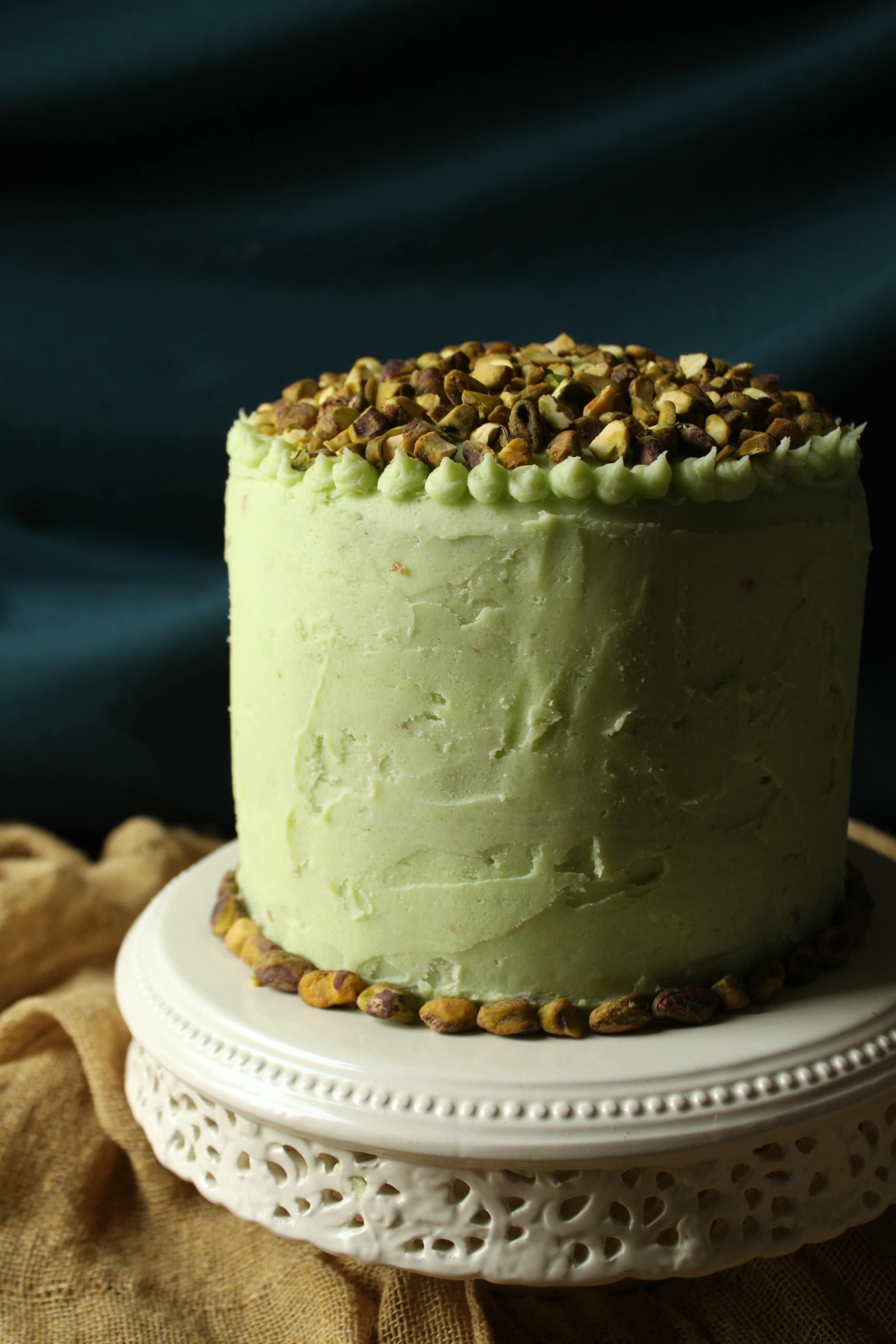This Chai Layer Cake with Pistachio Buttercream is sweet little cake with a whole lot of attitude. Recipe makes three 6 inch layer cakes and enough pistachio buttercream to sandwich between layers, cover the cake, and all some decorative touches. #birthdaycake #chaicake #layercake #pistachiobutercream