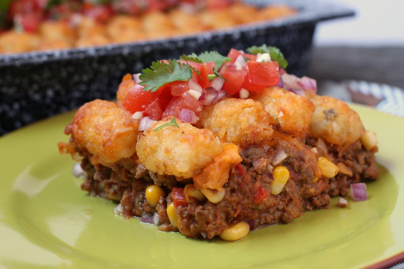 Everyone's favourite golden potato nuggets top a cheesy, comforting taco casserole made with ground beef, refried beans and veggies. #casserole #onepan #tatertots #tacospices #dinner #comfortfood